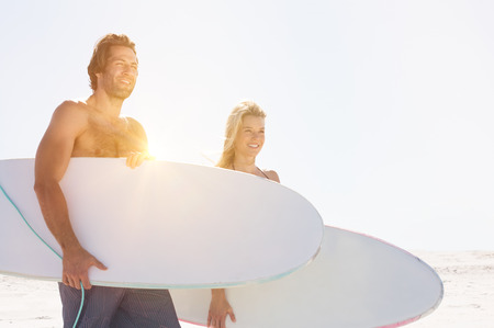 seaside: Young surfers couple with surfboards on the beach. Happy smiling friends standing on the coastline with surfboards. Happy couple surfing at beach.
