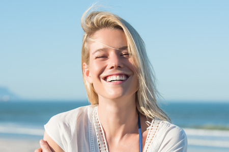 people laughing: Portrait of a young cheerful woman smiling at the beach. Young blonde enjoying on a bright sunny day at the beach. Portrait of happy girl laughing and looking at camera.