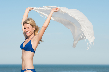 scarf beach: Beautiful young woman wearing blue bikini with flying scarf on beach. Carefree young woman on seaside looking at camera. Smiling girl on beach holding white scarf fluttering in the wind. Stock Photo