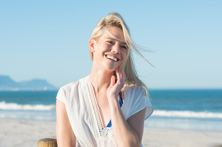 Portrait of happy smiling woman on the beach. Smiling sensual blonde posing on a beautiful wild beach. Pretty girl in casaul looking away and laughing. Stockfoto