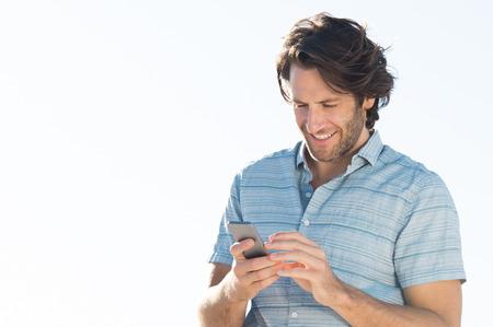 hombre escribiendo: Hombre joven hermoso que controla email en su teléfono inteligente. Joven sonriente y la lectura de un mensaje de teléfono al aire libre. Hombre joven en el teléfono usando ocasional, copia espacio. Foto de archivo