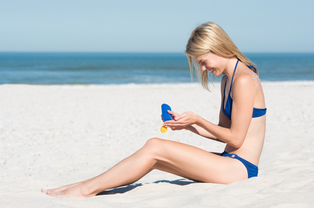 seaside: Portrait of a young woman sitting on white sand and applying suntan lotion. Blonde girl using sunscreen before enjoying sunbath. Beautiful young woman enjoying sunshine on summer vacation.