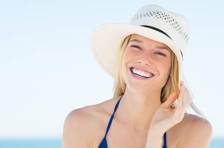 feeling good: Portrait of smiling  woman on beach wearing blue bikini and straw hat. Close up face of beautiful young woman feeling good at seaside. Happy girl wearing sun hat and looking at camera.