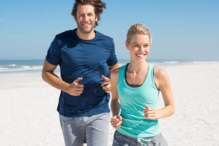 woman  smile: Couple exercising at beach. Trainer training athlete for fitness. Athletics jogging in summer sport shorts enjoying the sun.