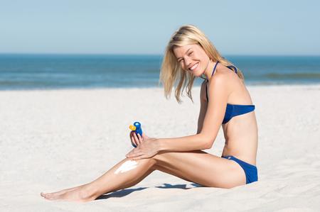 sun beach: Young woman in blue bikini sitting on sand and applying suntan lotion before sunbathing. Smiling young woman applying sunscreen on beach.