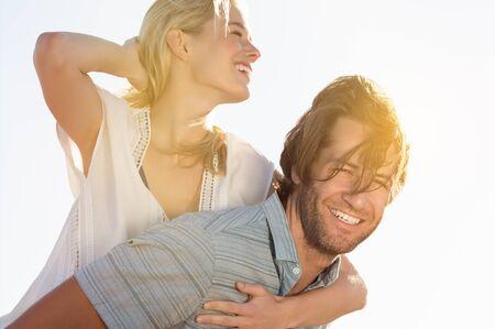 pareja abrazada: Feliz y alegre joven pareja a cuestas y divirtiéndose. hombre hispano latino joven que lleva a cuestas chica rubia en un día ventoso. sonriente pareja que se divierten al aire libre en un día de verano.