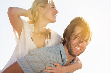blonde hispanic: Happy and cheerful young couple piggyback and having fun. Young latin hispanic man piggybacking blonde girl on a breezy day. Smiling couple having fun outdoor in a summer day.