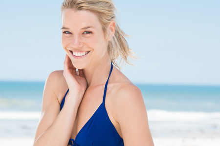 Portrait der attraktiven Frau, die am Strand stehen. Glückliches lächelndes Mädchen in die Kamera am Meer verbringen möchten. Junge blonde Frau am Strand entspannen.