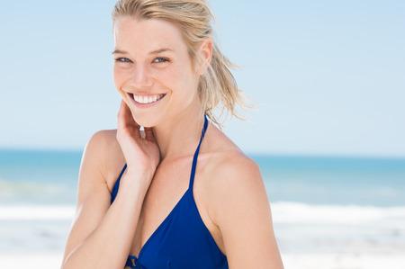 rubia: Retrato de la mujer atractiva en la playa. Feliz niña sonriente mirando a la cámara en la playa. Mujer rubia joven que se relaja en la playa.