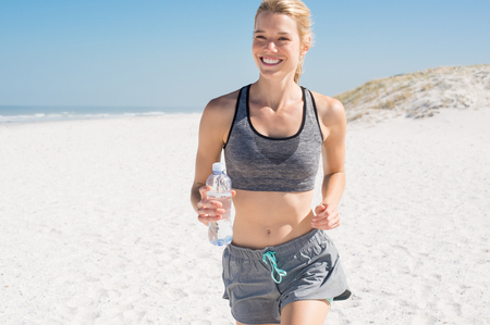 women smiling: Female runner jogging during outdoor workout on beach. Smiling woman running on beach. Beautiful fitness girl exercising outdoors with sea background. Stock Photo