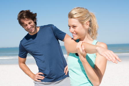 Young couple stretching at beach in a sunny day. Young woman and man working out in morning. Athlete couple exercising at beach in a summer day.