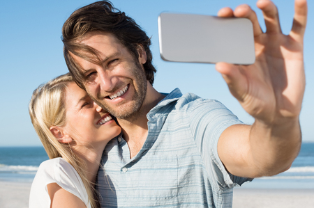 capturing: Happy smiling couple on the beach taking photo of themselves with smart phone. Young cheerful couple taking a selfie. Young couple embracing and capturing romantic moments with cellphone. Stock Photo