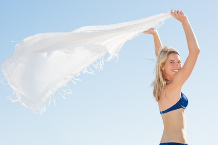 scarf beach: Woman waving white scarf in wind at beach. Young happy woman in bikini standing holding scarf in hand. Young woman playing with the scarf before going for a swim.