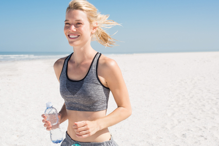 actively: Young woman jogging on the beach in summer day. Athlete runner exercising actively in sunny morning. Blonde girl preparing herself for marathon.