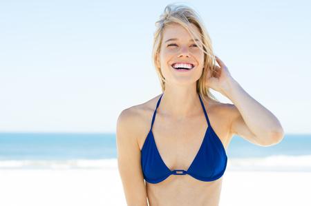 Fröhliche Frau im blauen Bikini Sommer am Strand genießt. Portrait der glücklichen jungen Frau Urlaub am Strand zu genießen. Smiling blonde Mädchen, das oben an der Küste mit Kopie Raum auf der rechten Seite. Standard-Bild - 54852455