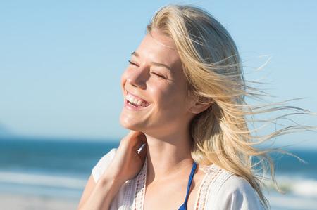 sonrisa: Retrato de reír a la mujer que toca su pelo. Alegre mujer atractiva disfrutando en la playa. Mujer alegre en la orilla del mar de risa. joven rubia en la orilla del mar con una sonrisa con dientes.