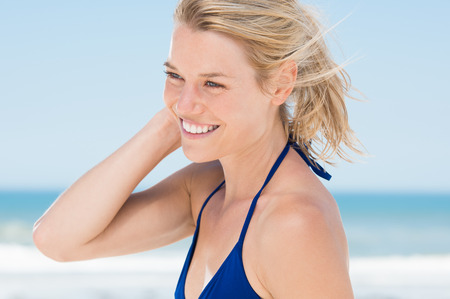 blonde bikini: Portrait of young woman sunbathing at beach. Woman refreshing herself at beach. Blonde girl with toothy smile with blue bikini at seaside. Stock Photo