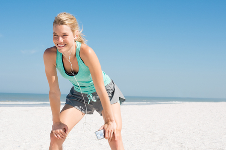 Young happy athlete tired after exercising. Woman resting at beach and listening to music after a routine workout. Young woman enjoying music at beach after run. Stock Photo
