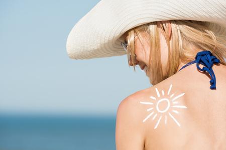 proteccion: Cierre para arriba de los hombros de la mujer hermosa con un sol dibujado con el bronceador. Actitud posterior de la chica que usa sombrero y gafas de sol en la playa. Hermosa mujer tomando el sol con un protector solar en el hombro.