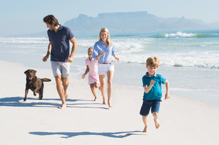 Family playing with pet on the beach. Happy beautiful family running at beach with pet dog. Smiling parents with son and daughter having fun at seaside.