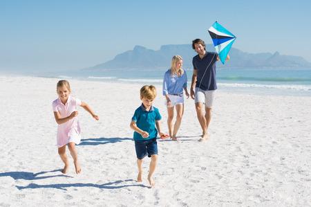 la familia feliz que se ejecuta en la playa con la cometa. Familia que disfruta de la cometa día volando en la playa. familia sonriente joven que juega en la playa.