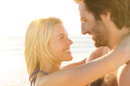 embracing couple: Attractive couple embracing on the beach on a sunny day. Young attractive couple in love. Loving couple embracing each other on the beach against ocean at sunset. Stock Photo