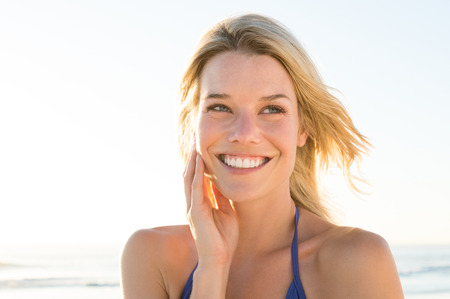 feeling happy: Portrait of happy young woman feeling good. Smiling young woman enjoying vacation at beach in a resort. Blonde girl thinking at beach and looking away. Stock Photo