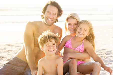 Portrait of smiling little boy with his family sitting in background at beach. Parents with children enjoying a holiday at the sea. Stock Photo