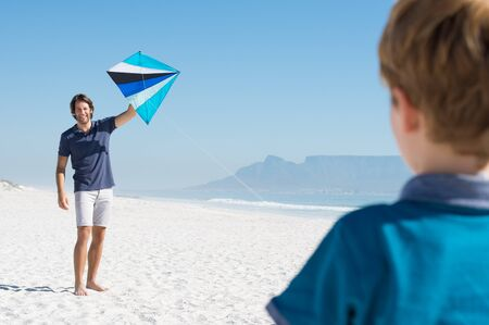 playful: Happy father getting ready to fly a kite with his son. Father helping his son to fly kite at beach. Man playing at beach with child.