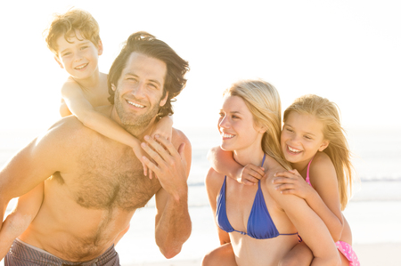 family vacation: Young family having fun at beach. Parents giving piggyback ride to kids. Portrait of smiling family looking at camera in a summer vacation at a resort beach.