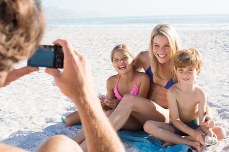 vacation summer: Father clicking picture of family at beach. Family posing for a photo during summer vacation. Cheerful mother sitting with son and daughter at beach for photo. Stock Photo