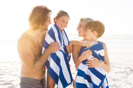 mamma e figlio: figlio bagnato e figlia avvolta in un asciugamano avvolgente dai genitori dopo la nuotata. Happy family in spiaggia dopo il bagno in mare tropicale. Padre sorridente e la madre di essiccazione i bambini con un asciugamani. Archivio Fotografico