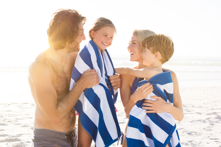 Natte zoon en dochter in een handdoek omarmen gedrapeerd door de ouders na het zwemmen. Gelukkige familie bij strand na zwemmen in de tropische zee. Glimlachende vader en moeder drogen van kinderen met een handdoeken. Stockfoto
