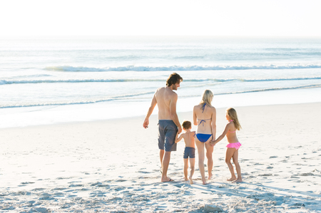 rear view: Back view of young family walking on beach at sunset. Rear view of family holding hands and walking towards sea to swim. Happy family enjoying holiday at beach.