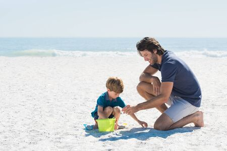 playful: Father and son playing with toys at beach. Family of father and son enjoying summer vacation at beach. Father helping son fill basket with sand.