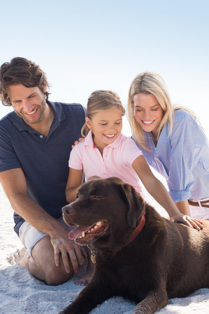 family happy: Happy young family at beach having fun with their dog. Family playing with their labrador retriever at vacation on a beautiful beach. Child with her parents stroking dog.