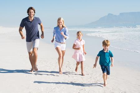 Familie, die am Strand. Happy schöne Familie Laufen und Blick in die Kamera. Glückliche Familie, die Spaß zu Fuß am Strand. Standard-Bild