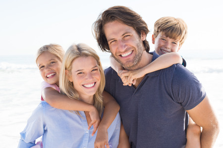 Parents giving piggyback ride to kids at beach. Close up of smiling family having fun at summer vacation. Portrait of happy family looking at camera at beach. Banque d'images
