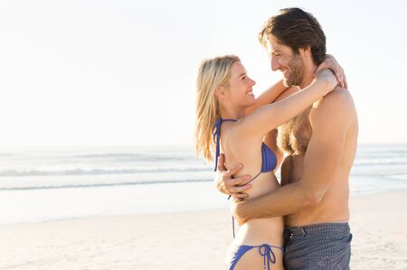 romantic beach: Loving couple in swimsuit embracing on the beach. Young couple in love looking at each other with sea in background. Romantic couple on sea shore with copy space.