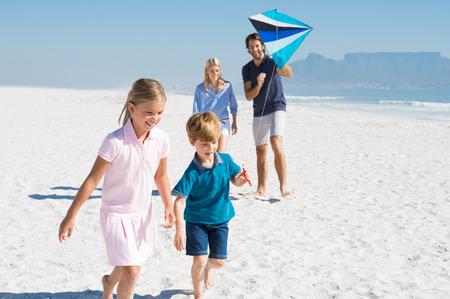 Glückliche Familie am Strand mit blauen Drachen läuft. Familie spielt mit Drachen in einem Sommerurlaub. Lächelnde Familie Drachen zusammen am Meer fliegen.
