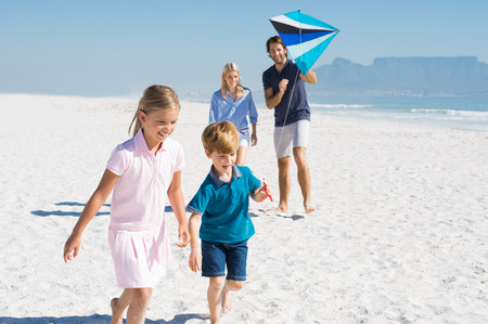 Happy family running at beach with blue kite. Family playing with kite in a summer vacation. Smiling family flying kite together at seaside. Banque d'images