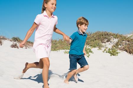niños riendose: Dos niños sosteniendo las manos que se ejecutan lejos en la playa de arena. Feliz sonriente niña y un niño lindo correr por las dunas en la playa. niños alegres corriendo descalzos en la playa.