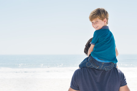 shoulder ride: Young boy sitting on father shoulder. Happy son enjoying shoulder ride at beach, copy space. Son looking at camera and smiling at beach. Stock Photo