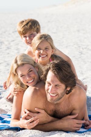 piramide humana: Retrato de la sonrisa de la familia acumuló en la playa. Familia feliz que se divierte en la playa. Los padres y los niños haciendo una pirámide humana en el mar.