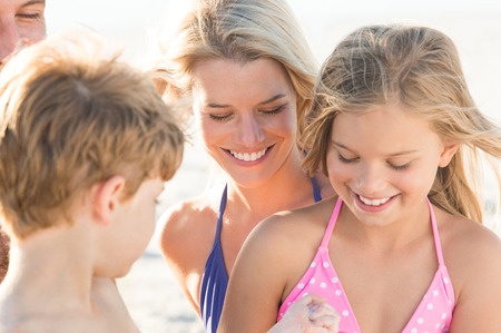petite fille maillot de bain: Les jeunes enfants qui jouent sur la plage avec les parents. Frère et soeur jouant avec des jouets à la station plage. Les enfants profitant de leurs vacances d'été en famille.