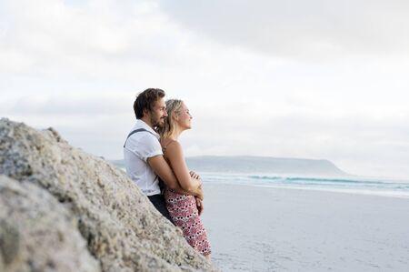 parejas enamoradas: Pares alegres jovenes en el amor que se inclina en la roca y mirando en el mar. Pares que se abrazan en la playa contra la roca. pareja alegre mirando la puesta de sol en la playa.