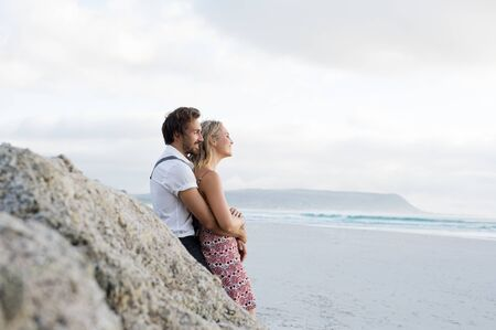 loving couples: Young cheerful couple in love leaning at rock and looking at sea. Couple embracing each other at beach against rock. Cheerful couple looking sunset at beach.