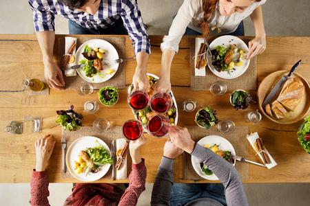 Bovenaanzicht van de groep van vrienden verhogen van een toast na de lunch. Hoge hoek mening van gelukkige mannen en vrouwen thuis vieren met rode wijn. Close-up shot van vrienden roosteren glazen rode wijn in een partij. Stockfoto