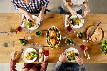 Top view of dining table with salad and roasted chicken with potatoes. High angle view of happy young friends having lunch at home. Men and women eating lunch together. Stock Photo