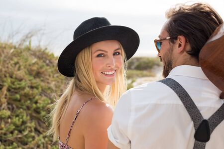 Portrait of happy young woman looking at camera. Cheerful woman wearing black straw hat while going at beach. Close up face of smiling girl with her boyfriend outdoor. Stock Photo